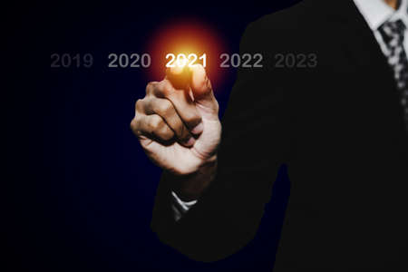 Goal target. businessman hand touching and pointing with pen on year 2021 with virtual screening on dark background, change from 2010 to 2021, strategy, business planning and happy new year concept