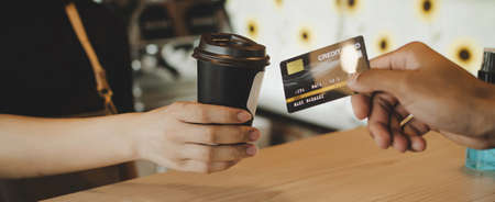 Panoramic banner. customer paying with credit card for buying black coffee on counter in cafe coffee shop, cafe restaurant, digital payment, small business owner, takeaway food, food and drink concept Stockfoto