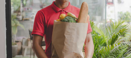 Panoramic banner. delivery man in red uniform holding fresh food set bag waiting for customer at door home, food delivery service, healthy food, express delivery, online shopping concept
