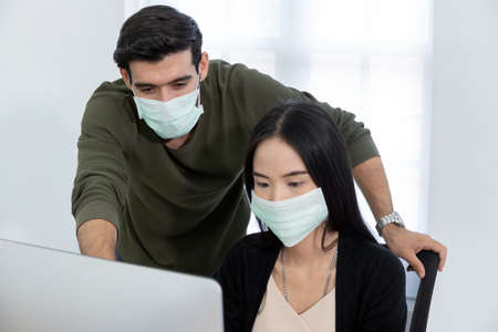 business people wearing protective face mask discuss project look at computer screen in meeting room office, intern new employee, creative, digital online marketing, business meeting startup concept Stockfoto