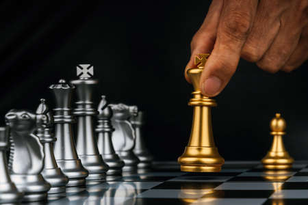 businessman hand moving gold king with silver chess pieces on chess board game competition on dark background, leadership, chess battle, management, team leader, teamwork and business strategy concept