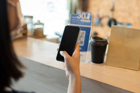 5G. customer using digital mobile phone scan QR code pay for buying coffee in modern cafe coffee shop, cafe restaurant, digital payment, online shopping, takeaway food, internet technology concept