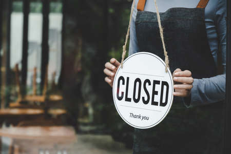 Closed. friendly waitress wearing protection face mask turning open sign board on glass door in modern cafe coffee shop, cafe restaurant, retail store, small business owner, food and drink concept