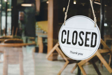 Closed. coffee cafe text on vintage sign board hanging on glass door in modern cafe coffee shop, reopening cafe restaurant, retail store, small business owner, takeaway food, food and drink concept