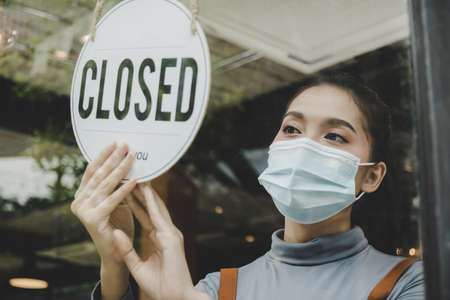 Reopen. friendly waitress wearing protection face mask turning closed sign board on glass door in modern cafe coffee shop, cafe restaurant, retail store, small business owner, food and drink concept