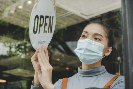 asian small business owner woman wearing protection face mask turning open sign board on glass door for reopening cafe restaurant after coronavirus (covid-19) quarantine. food and drink concept 版權商用圖片