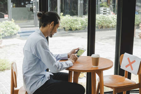 businessman using mobile tablet with hot coffee cup on desk sitting with paper sign on seat and keep distance to protect infection coronavirus (covid-19) in cafe restaurant, social distancing concept 版權商用圖片