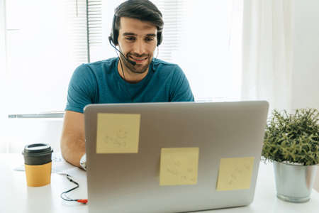 young happy handsome man student wear headphone listen online course communicate from home, corona virus (covid-19) outbreak, video call conference, education, internet and technology concept 版權商用圖片