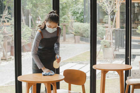 asian waitress staff wearing protection face mask in apron cleaning table with disinfectant spray for protect infection coronavirus (covid-19) in cafe coffee shop restaurant. new normal concept 版權商用圖片