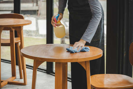 asian waitress staff service woman in apron cleaning table with disinfectant spray for protect infection