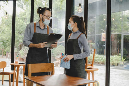 asian waitress staff team service wearing protection face mask for protect infection in apron attending team meeting in cafe coffee shop restaurant. new normal concept 版權商用圖片