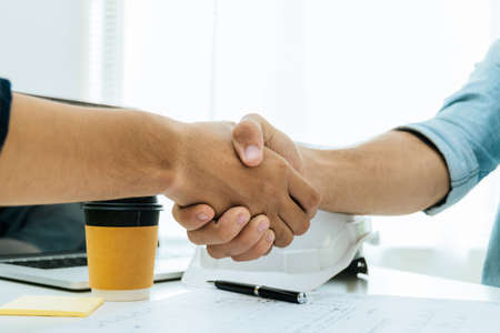 engineer, architect, construction worker team hands shaking after plan project contract on workplace desk in meeting room office at construction site, contractor, partnership, construction concept 版權商用圖片