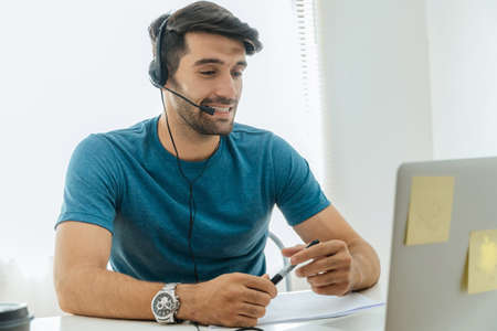 young happy handsome man student wear headphone listen online course communicate from home
