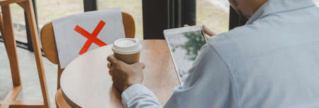 wide banner. businessman using mobile tablet on desk sitting with paper sign on seat and keep distance to protect infection in cafe restaurant, social distancing concept