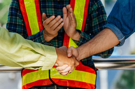 Partnership. team of construction worker shaking hand with customer after finishing up business meeting to greeting start up project contract at construction site, business and contractor concept 版權商用圖片