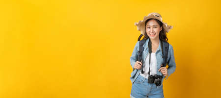 asian pretty woman gamer in casual clothing smiling and playing video game with mobile phone on copy space area on yellow panoramic wide background, game online, entertainment and technology concept