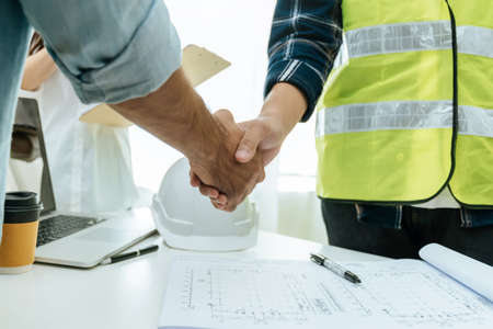 construction worker team contractor handshake after finishing business meeting to start up project contract in construction site building, construction teamwork, partnership and industry concept