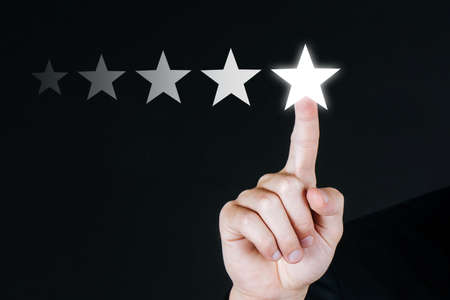 5 star rating. business customer hand pressing five star button on visual screen to review good rating with copy space on dark background, good experience, positive thinking, customer feedback concept