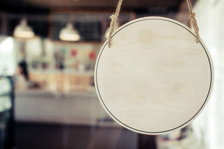 blank vintage wooden sign board hanging on glass door in modern cafe restaurant, copy space for text advertising, advertisement marketing and small business owner concept Stock Photo