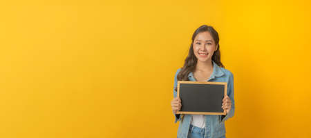 wide banner. happy asian pretty woman in casual clothing smile, hold empty blank blackboard with copy space area for text on yellow background, online marketing, advertising, announcement concept Stock Photo