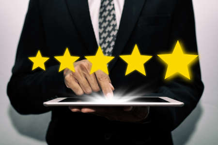5 star rating. business man customer hand touching on mobile tablet with five star button to review good rating, digital marketing, good experience, positive thinking and customer feedback concept Stock Photo