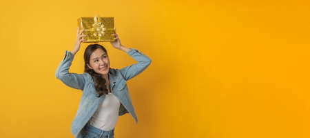 Happy birthday. wide banner. happy asian pretty woman in casual clothing jeans smiling and hold new year gift box over copy space yellow color background, christmas celebration, happy hew year concept