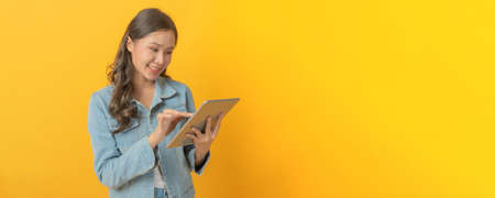 young asian pretty woman smiling using mobile tablet computer on copy space area on yellow panoramic wide background, business finance, online marketing, entertainment and internet technology concept Stock Photo