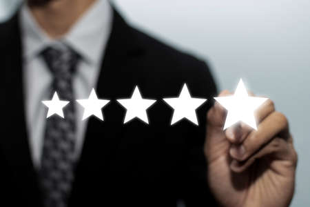 5 star rating. business man customer hand pointing on five star button on visual screen to review good rating, digital marketing, good experience, positive thinking and customer feedback concept Stock Photo