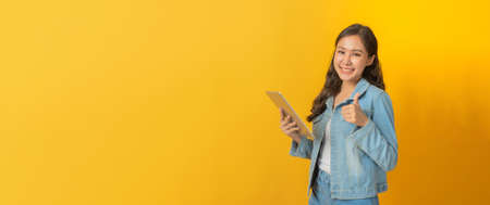 asian pretty woman showing thumbs up using mobile tablet computer on copy space area on yellow panoramic wide background, business finance, online marketing, entertainment, internet technology concept Stock Photo