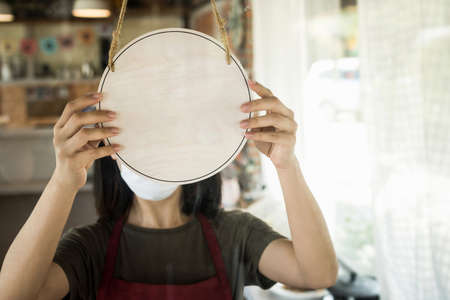 woman wearing protection face mask turning blank wooden sign board hanging on glass door in cafe restaurant, advertising, advertisement marketing and small business owner, food and drink concept