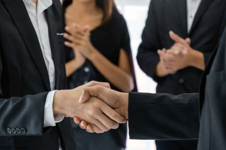 business people group handshake and clapping hand after finishing up business meeting in office, congratulation on promotion, Partnership, success, partner, teamwork, community, connection concept Stock Photo