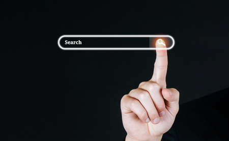Searching. business customer hand pressing visual screen search button with copy space on dark background, searching browsing information, internet data technology and data search engine concept Stock Photo