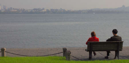 Chinese couple sitting on a bench and looking the lake photo