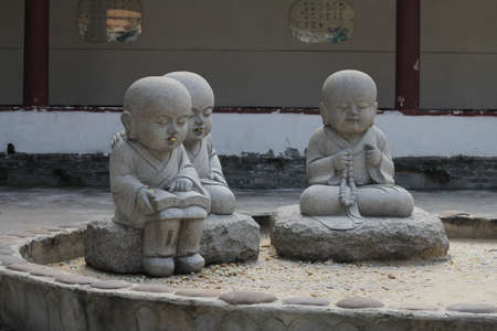 eastern spirituality: Little monks with peanuts in their mouths in a Chinese Buddhist temple