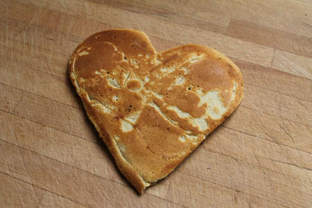 A pancake shaped as a heart, on a wooden table  A sweet way to say I love you photo