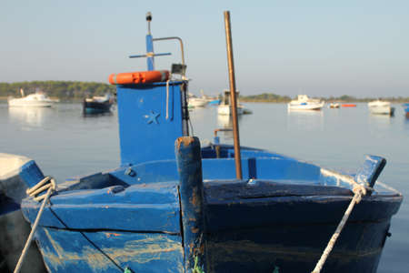 Docked blue fishing boat in a small village in the south of Italy photo