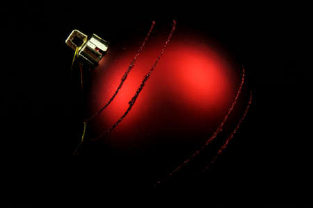 dim light: Red Christmas bulb with black background and dim light  Stock Photo