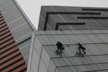Men cleaning skyscraper windows, climbing with ropes in China