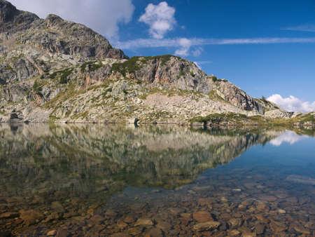 Mountains reflect on small alpine lake on the Bergamo Alps, northern Italy