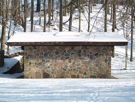 snow on a rock cabin photo