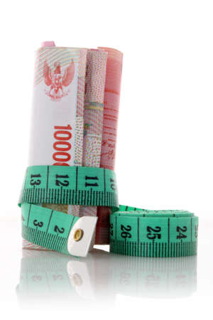 Green  tailor meter with money on white