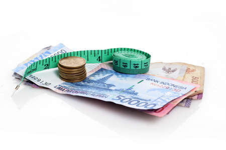 rupiah with measure tape, on white background, with reflection Stock Photo