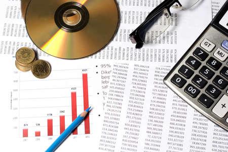 zakelijke grafiek, lenzenvloeistof, blauw potlood, munten, CD, DVD, rekenmachine Stockfoto