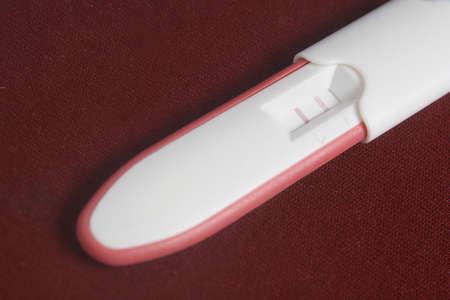 prueba de embarazo: Embarazo Pack de Prueba En El Fondo Rojo Oscuro