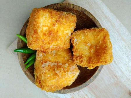 Flache Lagen oder Draufsicht, Tahu Sumedang (Fried Tofu) aus West Java, Indonesien mit grünem scharfem Chili in einer kleinen Holzschüssel