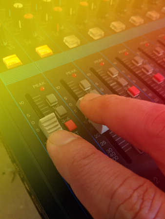 Close Up Man Hand Controlling Audio Mixer, with yellow and Red Light Flare