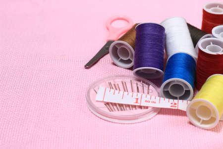 Flat lay or top view, Needle Scissor, Thread, Tailor Meter, Scissor at Pink Background