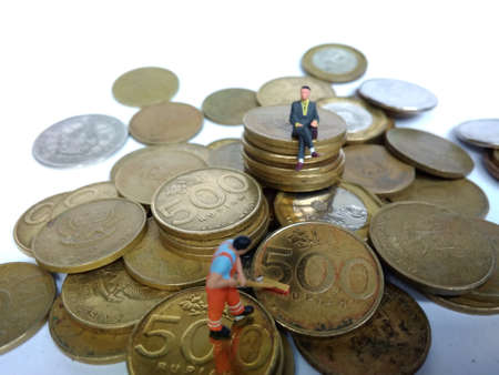 conceptual Illustration for Money Laundry Activity, worker mini figure toy cleaning golden indonesia rupiah coin Foto de archivo - 104932201
