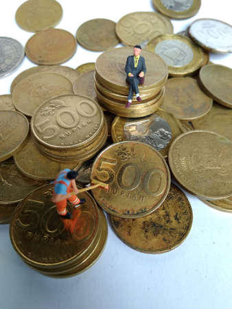 conceptual Illustration for Money Laundry Activity, worker mini figure toy cleaning golden indonesia rupiah coin Foto de archivo - 104908732