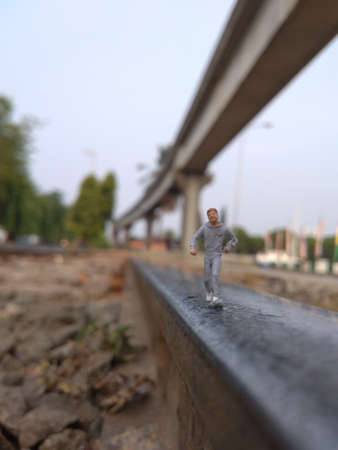 Running Mini Figure man in the morning, at jogging track at the train track